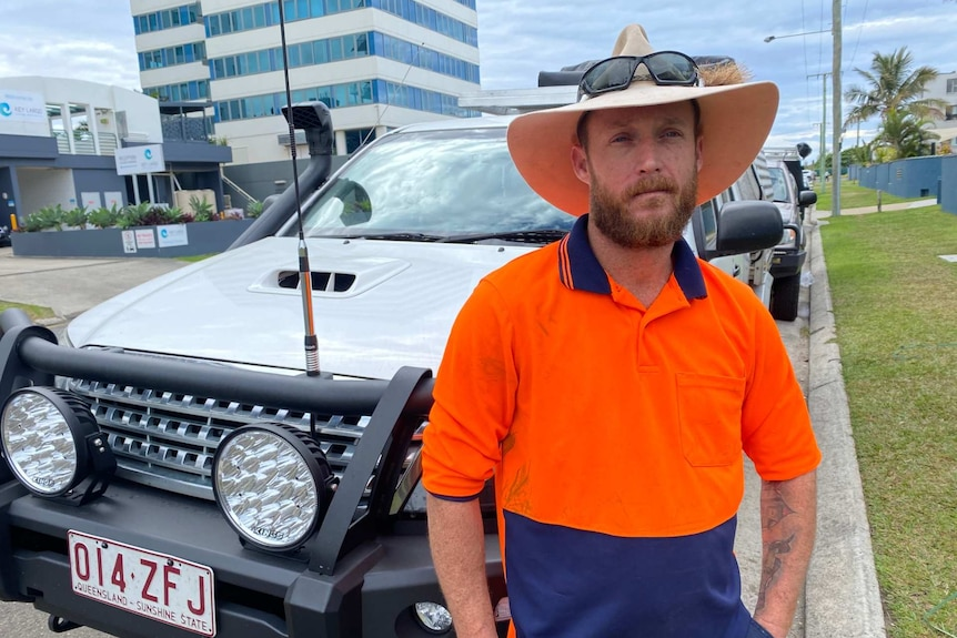 Stuart Pope in a fluroscent orange work shirt and wide brimmed hat sitting on a white vehicle