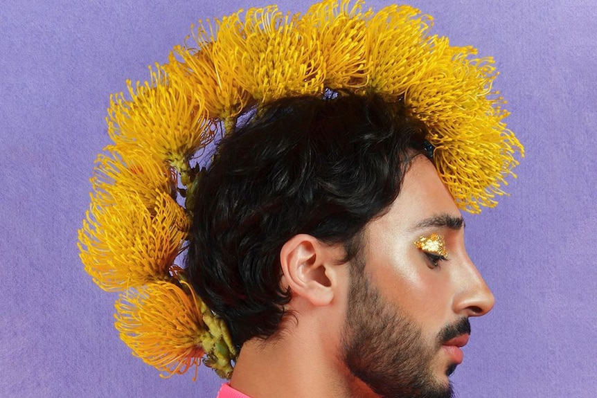A man stands side on with yellow flowers shaped into a mohawk with gold eye shadow.