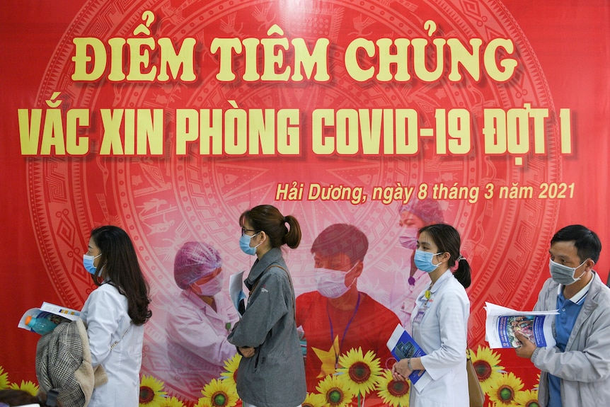 Health workers wait for their turn to be vaccinated in front of a red banner