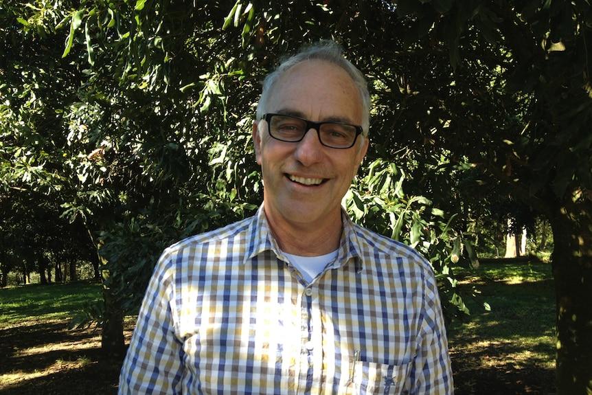 Jolyon Burnett smiling at the camera in a macadamia orchard.