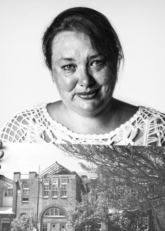 A woman holding a photograph looks at the camera.