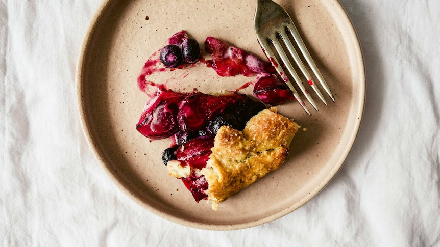A slice of summer galette with stone fruit and blueberries on a plate, an easy dessert recipe.