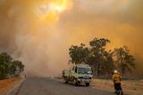 Smoke fills the sky and landscape as two firefighters stand near a fire truck  on a road and another sprays bushland.