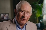Prince Charles sits in a living room, with family photos in the background.