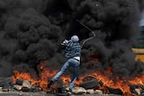 A man fires a slingshot from behind black smoke caused by burning tyres