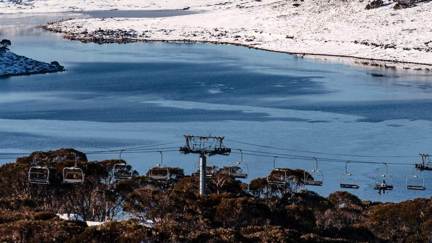 Falls Creek with some snow, a body of water and some chairlifts