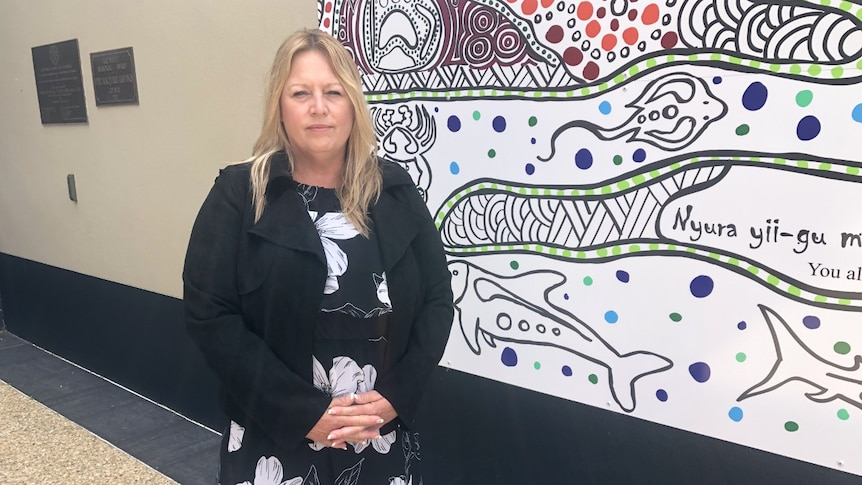 A blonde woman in a dark cardigan standing in front of an Indigenous painting.