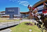 A sign for Bunjil Place is shown in front of a large multi-storey modern building.
