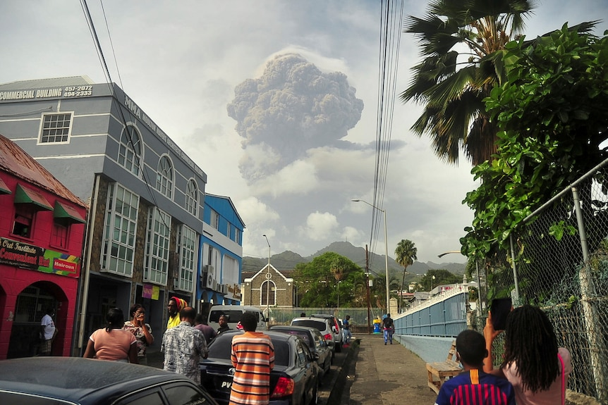 People in a street in a town look at a plume of ash in the distance.