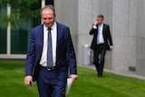 Deputy Leader Barnaby Joyce walks in the courtyard of Parliament House with his head down