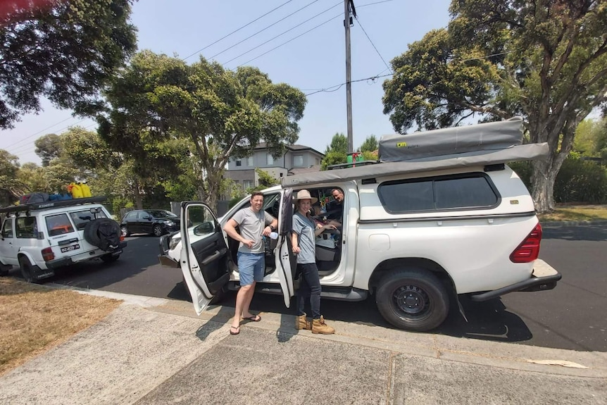 Mr O'Connor and his family smile at camera, leaning on their 4WD hire.