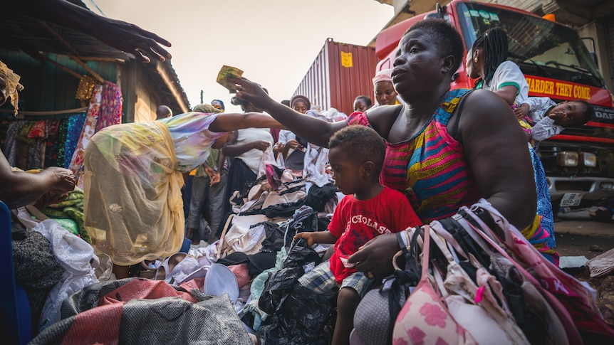 A woman buys clothes in Kantamanto Market, Accra.