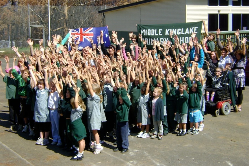 A group of primary school kids in uniform stand outside portable classrooms and cheer with hands in the air.