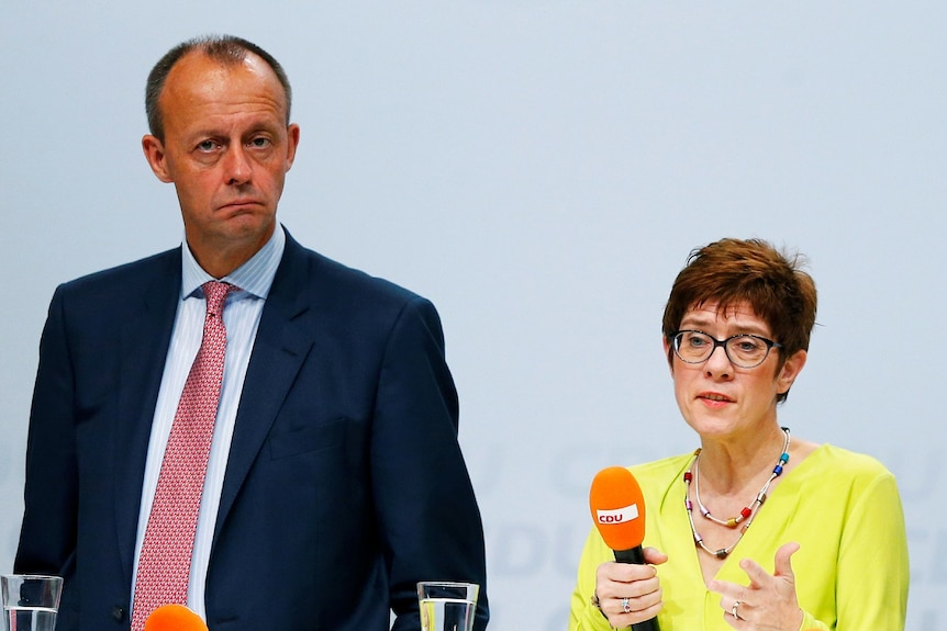 Two tall men and one quite short women stand on stage, the woman is holding an orange microphone.