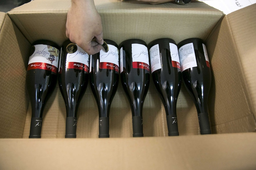 A worker places stickers on wine bottles at Shiloh Wineries.