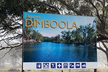 a blue sign that says dimboola with a picture of  lake. the sign is in front of scrub land with fog