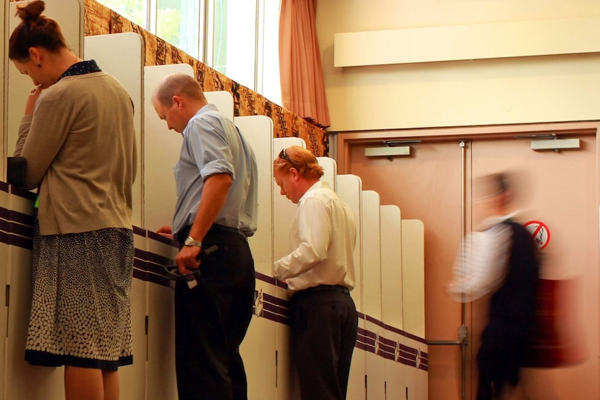 Three unidentified voters at a polling booth and a blurry walking figure heads to cast vote