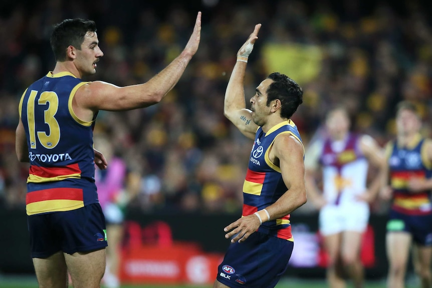 Two AFL players give each other a high five