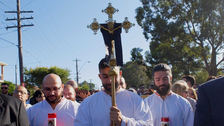 Three Maronite altar servers dressed in white robes bow their heads. One holds gold cross.
