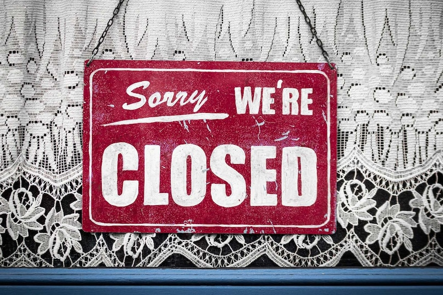 Sorry we're closed sign hanging in store window.