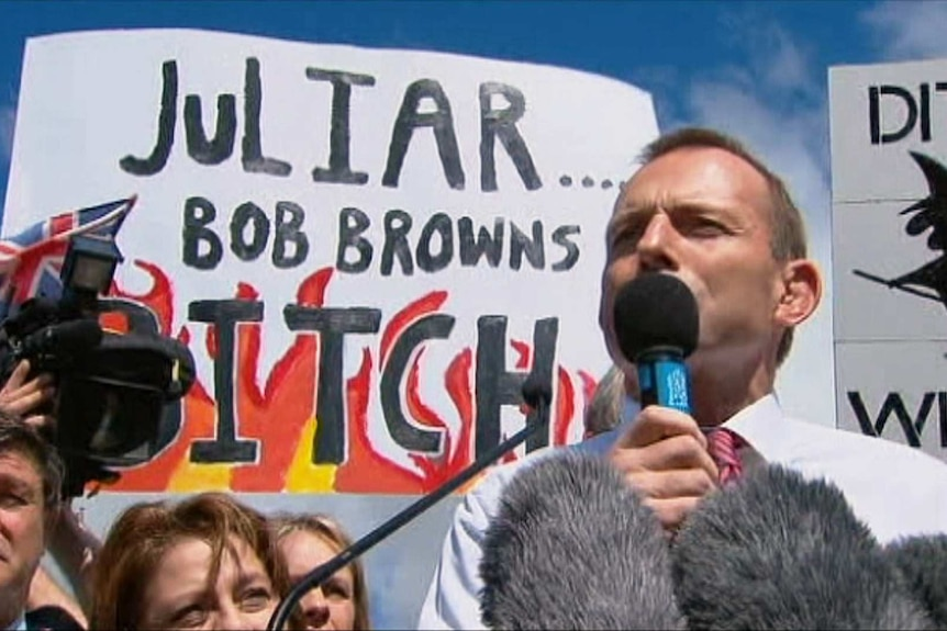 Tony Abbott stands in front of an anti-Julia Gillard protest sign