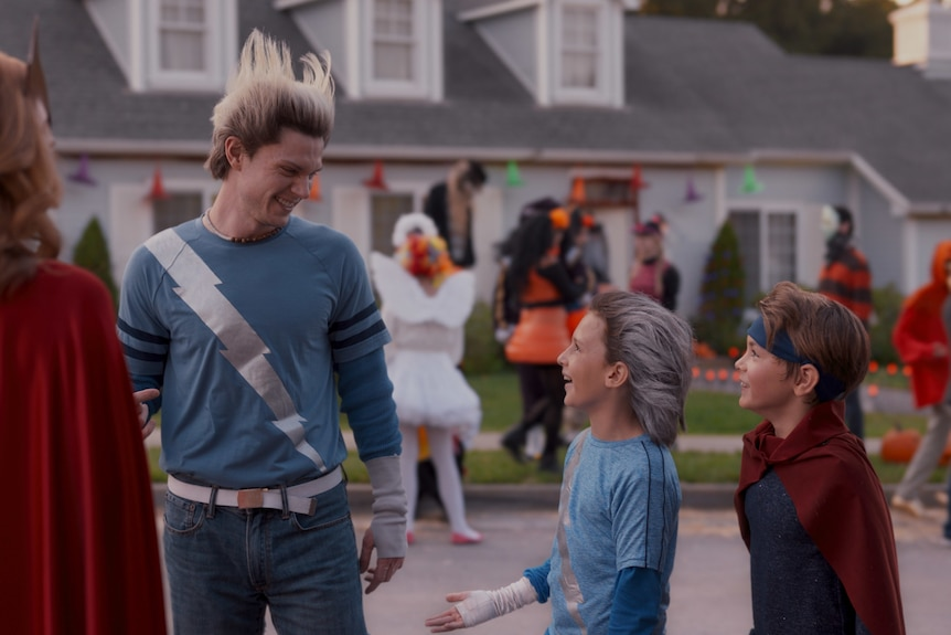 All dressed in superhero costumes, a woman faces away while a 30-something man smiles down at two children on Halloween.