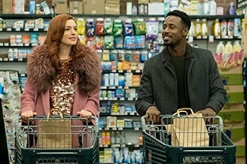 Anne Hathaway and Gary Carr push trollies side by side in the supermarket
