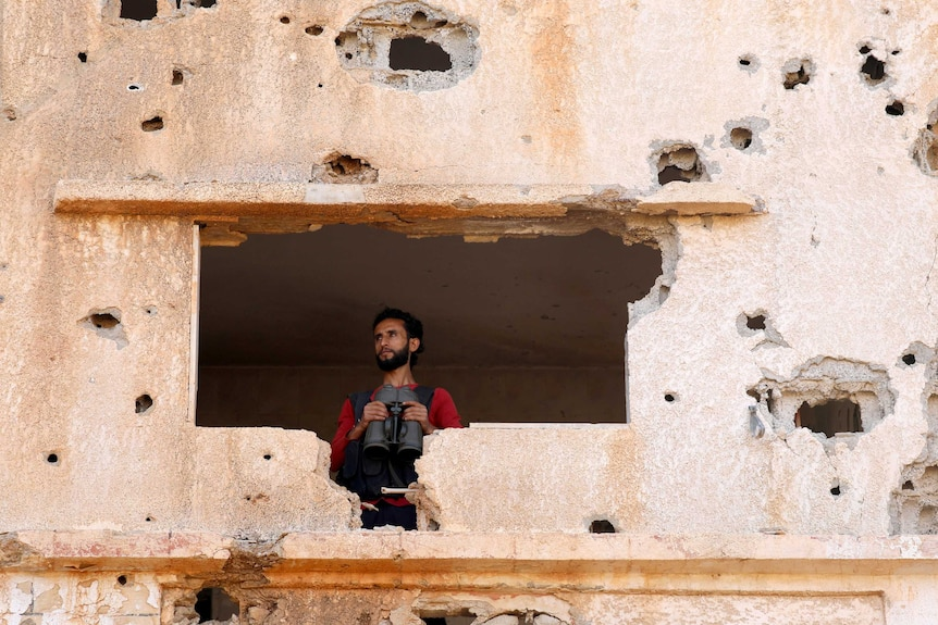 A Free Syrian Army fighter looks through a hole in a bullet punchered wall in Yadouda, Daraa