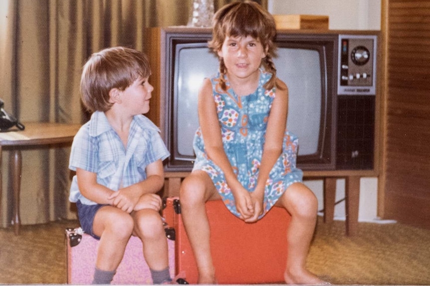 A young girl and boy sit on suitcases in a living room