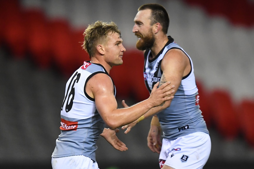 Two Port Adelaide AFL players shake hands as they celebrate a goal against St Kilda.
