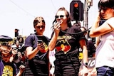 A woman wears an t-shirt with an indigenous flag and yells into a microphone at a protest
