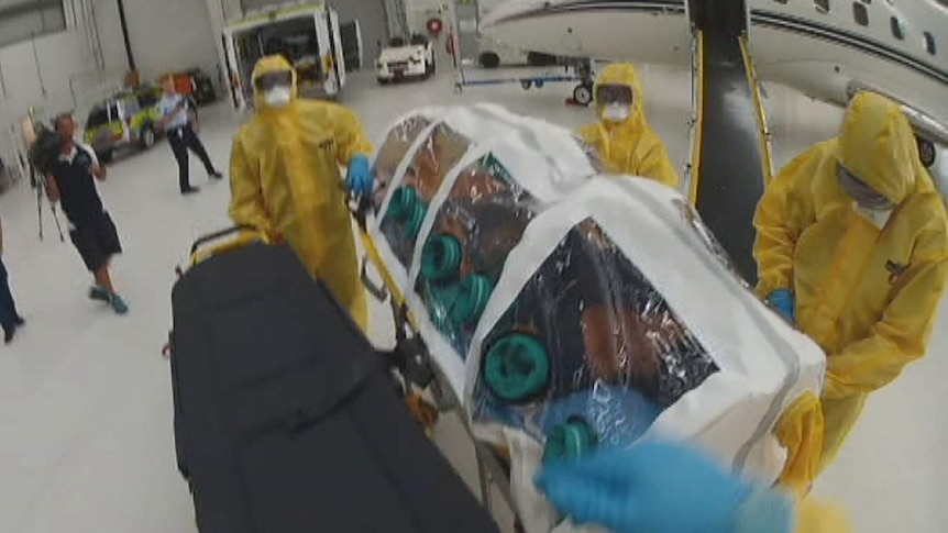 A mock Ebola patient in an isolation unit is transferred from a plane at Brisbane Airport.