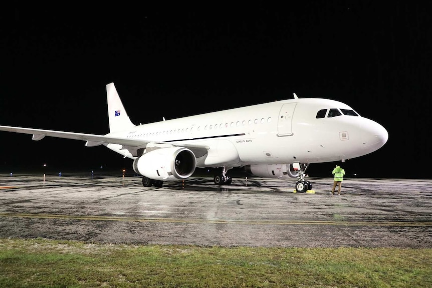 A white plane on the tarmac at night.