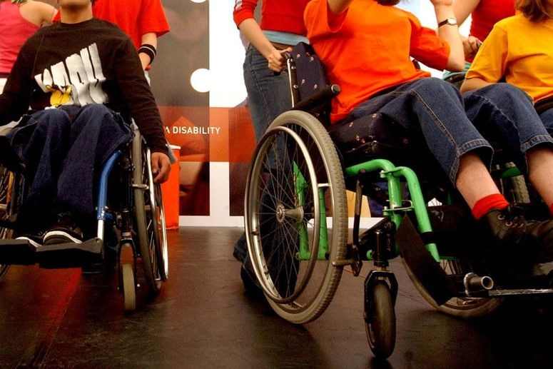 People in wheelchairs on a stage.
