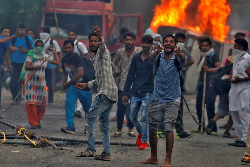 A group of men riot in front of a burning vehicle.