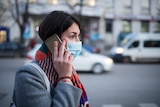 Young woman wearing face mask on phone.