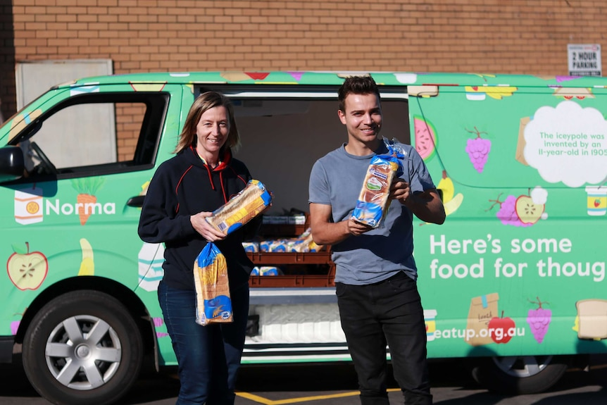 A woman and man hold bread loaves in front of the Eat Up van