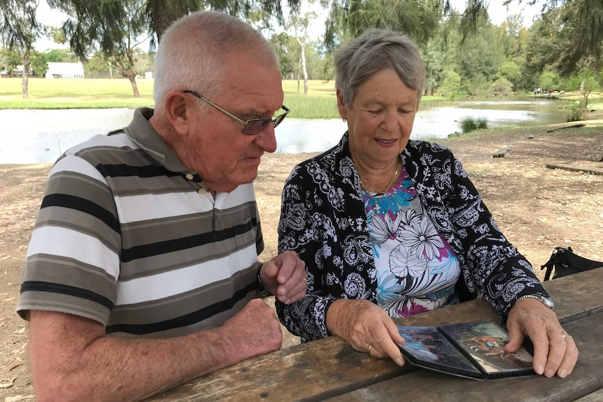 An elderly couple looking through a photo album in a park with a lake and trees in the background.