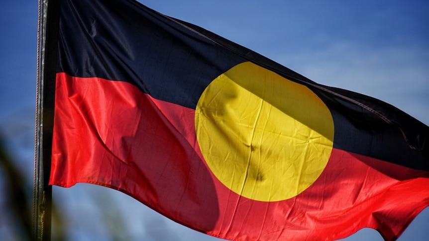 The Aboriginal flag flies against a blue sky.