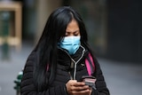 A woman wearing a mask and a winter coat looks down at her phone.