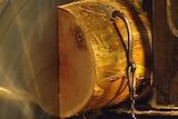 An electric saw going through a log