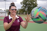 Woman with sunglasses, smiles as she catches a netball.