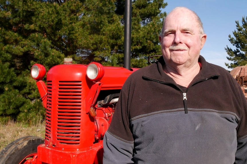 An elderly man stands in front of a tractor, looking at the camera.