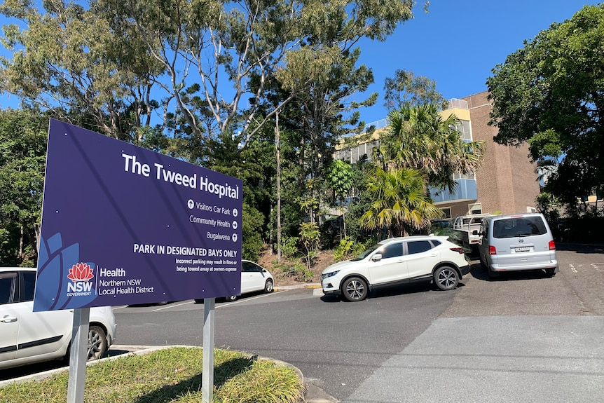 """A blue sign in the carpark that reads """"The Tweed Hospital,"""" cars and building in background"""