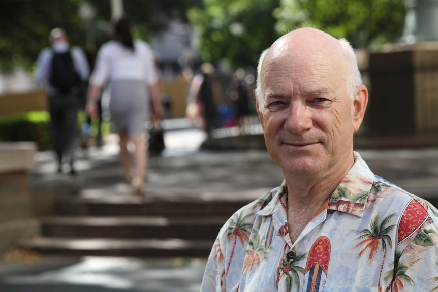 A bald, white haired man wearing a Hawaiian shirt looks at the camera, smiling, while standing outside on a sunny day.