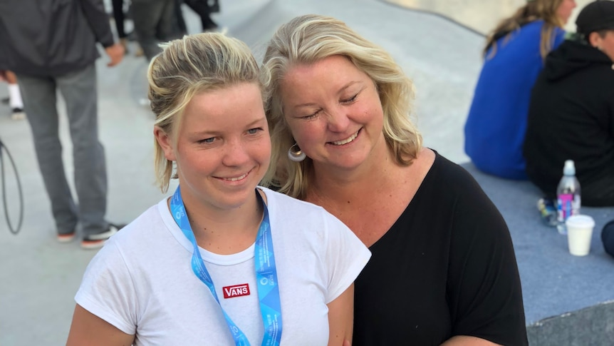 Exterior beside a skate bowl Poppy showing a medal hugged by her mum Thomas