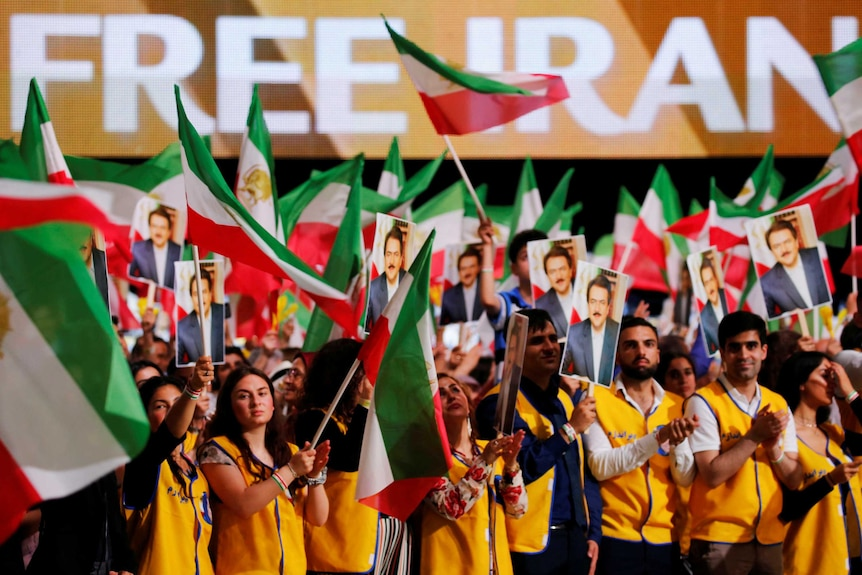 """People wave flags with """"Free Iran"""" written on screens in the background."""