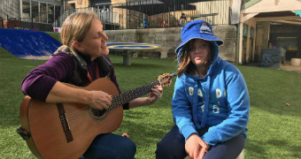 A lady in a purple jumper plays guitar with a disabled teenager wearing a blue jumper and matching bucket hat