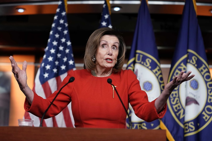 Nancy Pelosi shrugs her shoulders while speaking behind a lectern in front of US flags.