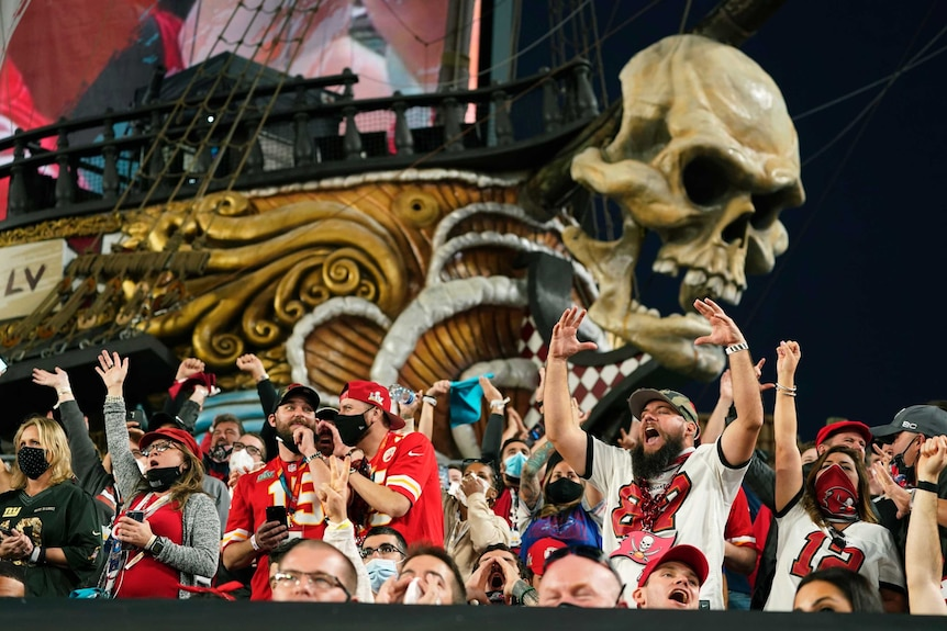 Super Bowl fans cheer in front of a pirate ship adorned with a skull at a stadium in Tampa.